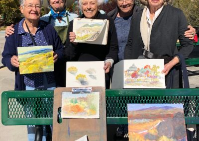 five women posing with their finished artwork