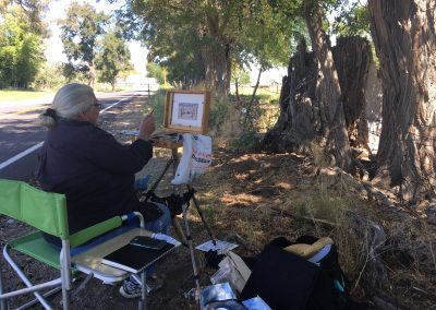 Member painting the trees on a plein air paint out.